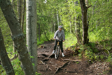 woman mountain biking on an Alaska forest trail
