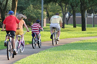family cycling in a Sugar Land, Texas park